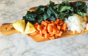 Cutting board with chopped sweet potato, kale, onion, and sliced lemon