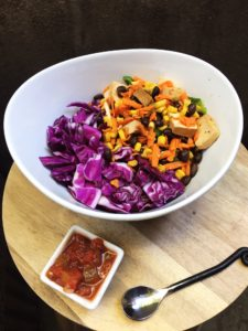 Big colorful bowl of veggies with a side of salsa