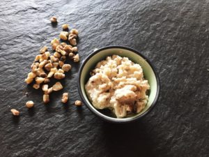 Bowl with vegan ice cream next to sprinkled black walnuts